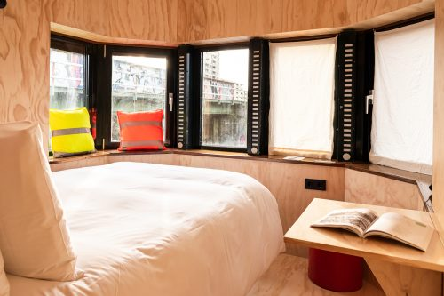 Bed, seating area and windows of SWEETS hotel's bridge house Omvalbrug