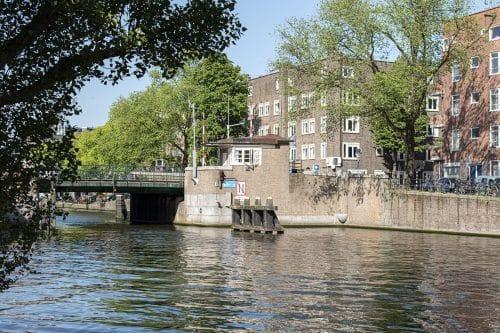 Photo of SWEETS hotel Amsterdam West Van Hallbrug bridge house exterior hotel near Amsterdam Center neighborhood green trees sunny