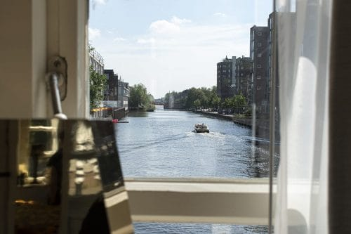 Photo of SWEETS hotel Amsterdam West Van Hallbrug bridge house interior hotel near Amsterdam Center view from bedroom window view boat passing by summer