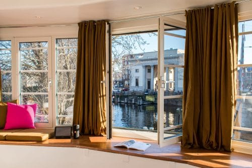 Windows open with view of the canal at SWEETS hotel's bridge house Willemsbrug