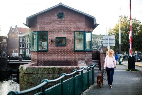 Kattensloot Amsterdam bridge house, woman walking dog, Amsterdam bridge house