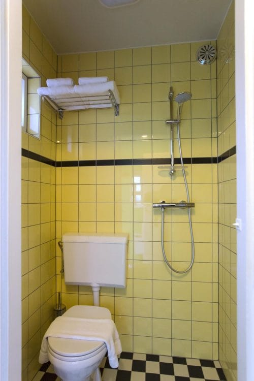 SWEETS hotel Beltbrug bridge house on Amsterdam canals - yellow bathroom with toilet and shower